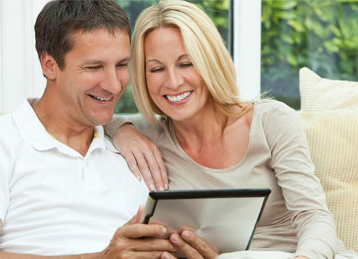 A happy couple looking at a tablet